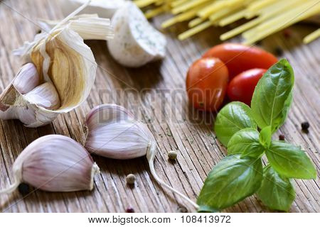 closeup of some garlics, a twig of mint, some cherry tomates and a pile of uncooked spaghetti on a rustic wooden table, ready to prepare a meal