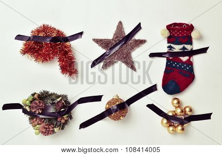 some different christmas ornaments, such as tinsel, a star, a stocking or baubles, attached to a white wall with black tape