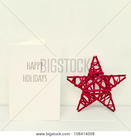 a rustic red Christmas star and a white greeting card with the text happy holidays in a white scene