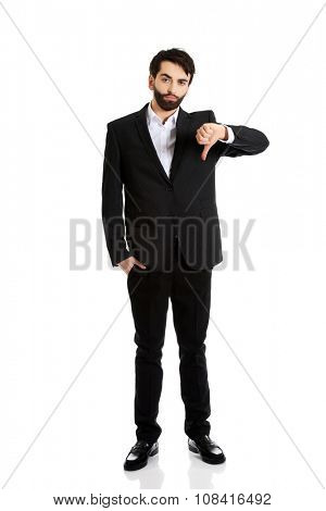 Unhappy sad businessman with thumbs down gesture.