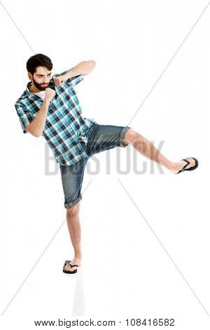 Young fit casual man kicking.