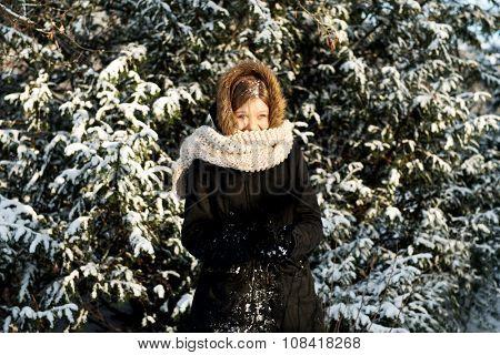 Happy teenage woman making snowball