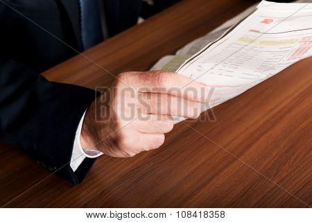 Mature businessman hand with newspaper.