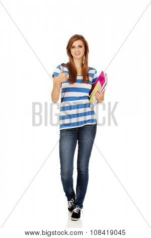 Young smiling teenage woman holding books.