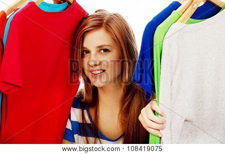 Happy teenage woman between clothes on hanger.