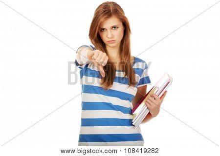 Teenage woman holding a books and shows thumb down.