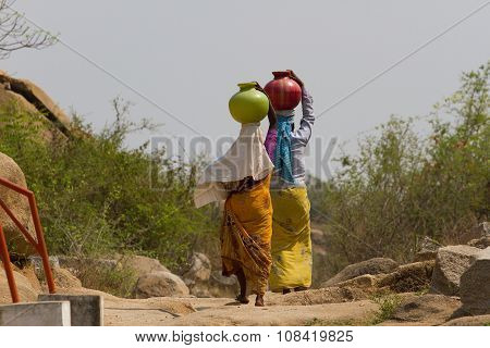 Two Indian women carry water on their heads in  pots