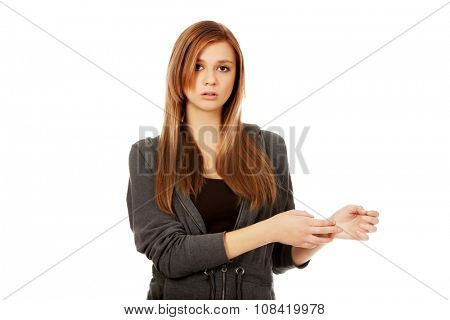Teenage woman holding her wrist - pain concept.