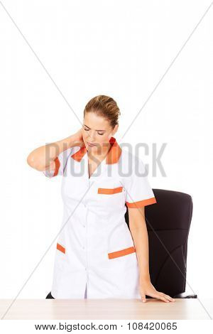 Tired young female doctoror nurse standing behind the desk.