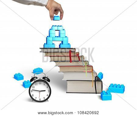 Hand Completing A Shape Blocks On Books Stairs Alarm Clock