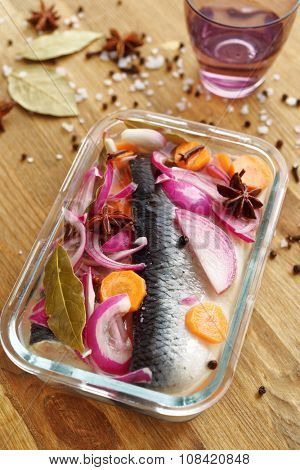 Marinated herring with onion and spices in a glass bowl