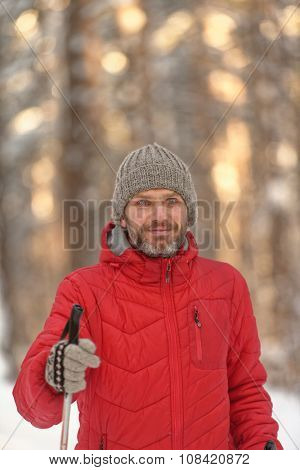 Mature man in red jacket cross-country skiing