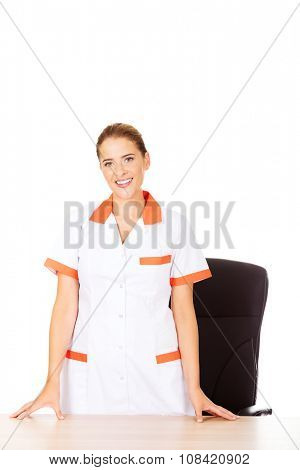 Young smile female doctor or nurse standing behind the desk.