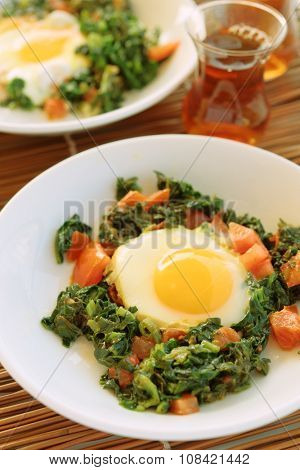 Fried egg with spinach and tomato on a Turkish dinner table