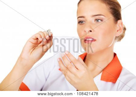 Young female dentist holding a tooth model and dental mirror.