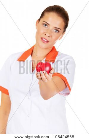 Young female doctor or nurse holding toy heart.