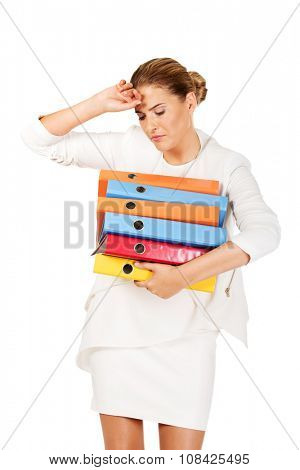 Tired businesswoman carrying heavy binders.