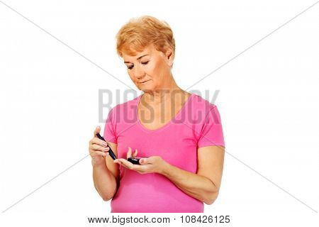 Senior woman with glucometer checking blood sugar level.