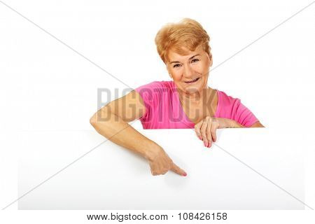 Smiling senior woman pointing for something on empty banner.