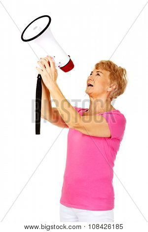 Senior smiling woman screaming through a megaphone.