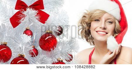 portrait of attractive  caucasian smiling woman blond isolated on white studio shot in santa's hat and red dress new year tree red balls