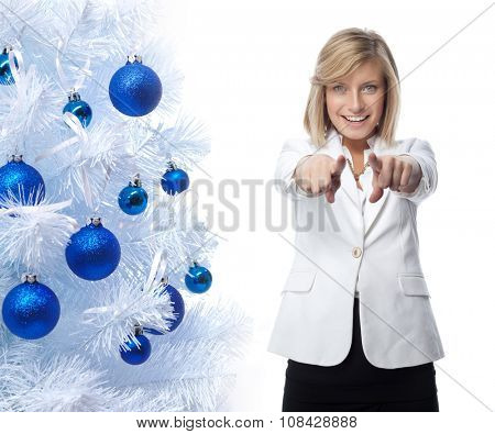 portrait of attractive  caucasian smiling woman isolated on white studio shot looking at camera pointing to new year christmas tree blue balls