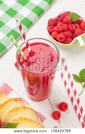 Raspberry smoothie, cake and berries on wooden table