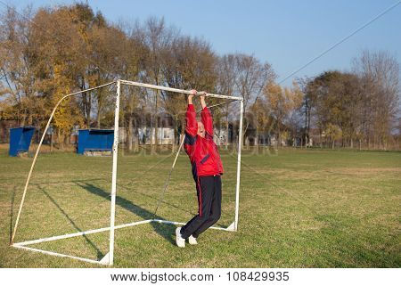 Old Man Exercising On Soccer Field