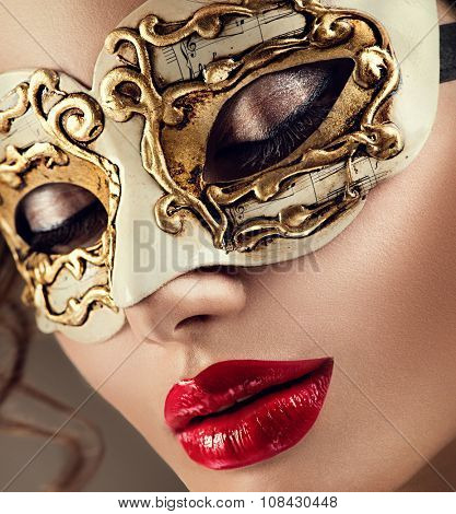 Beauty model woman wearing venetian masquerade carnival mask at party over holiday dark background. Christmas and New Year celebration. Glamour lady with perfect make up