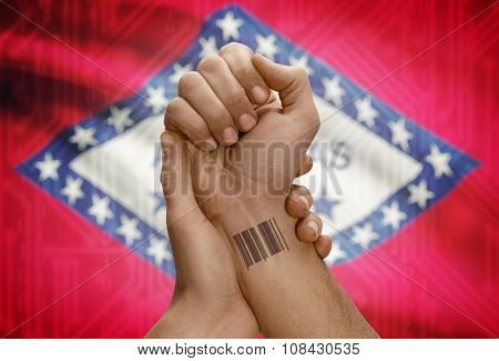 Barcode Id Number On Wrist Of Dark Skinned Person And Usa States Flags On Background - Arkansas