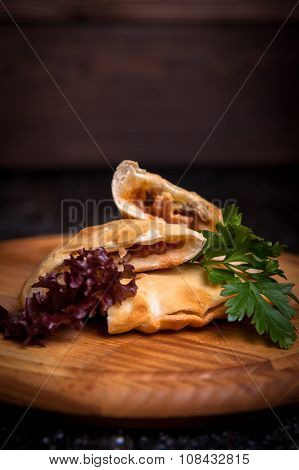 Aromatic strudel cut lies on a wooden Boards with herbs