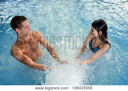 Couple In Love Laughing And Playing With A Cascade Of Water