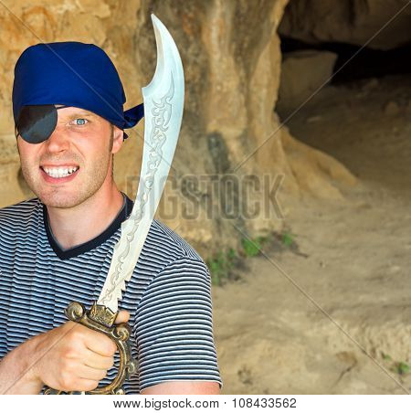 Angry Male Pirate With Sword Near The Cave Entrance. Place For Your Text.