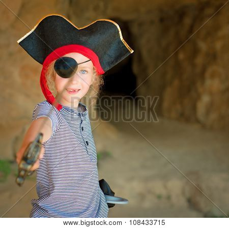 Little Girl In Pirate Costume With Sword Near The Cave Entrance.