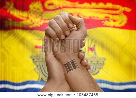 Barcode Id Number On Wrist Of Dark Skin Person And Canadian Province Flag On Background - New Brunsw