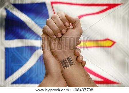 Barcode Id Number On Wrist Of Dark Skin Person And Canadian Province Flag On Background - Newfoundla