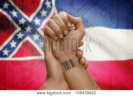 Barcode Id Number On Wrist Of Dark Skinned Person And Usa States Flags On Background - Mississippi