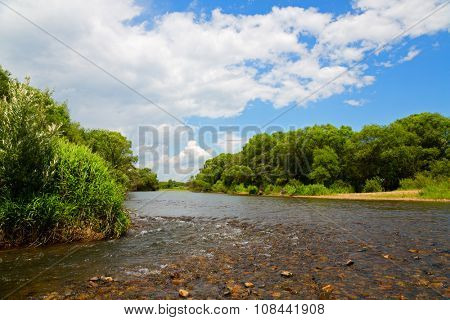River summer landscape with blue sky and clouds. Far East, Russia.