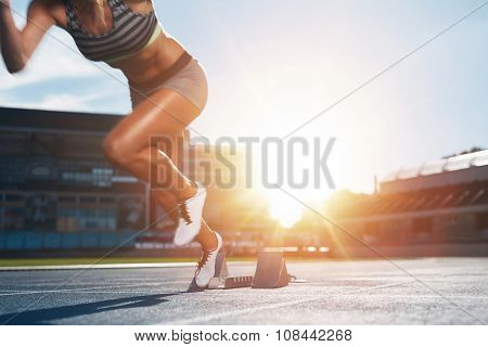 Female Athlete Launching Off The Start Line In A Race