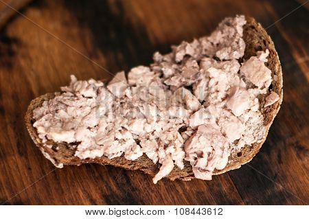 Black bread with cod liver is on the board