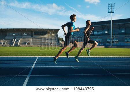 Young Men Running On Race Track