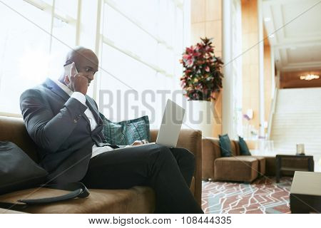 Businessman Sitting In Hotel Lobby Using Cell Phone And Laptop