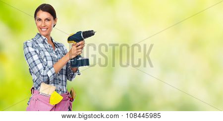 Young woman with a drill. House renovation green background.