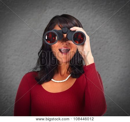 Business woman with binoculars over gray wall abstract background.