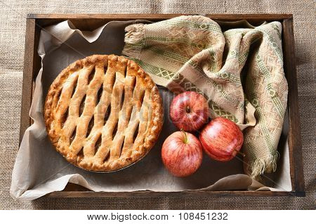 High angle view of a fresh baked apple pie and apples in a wood box on burlap surface.