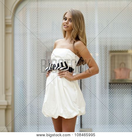 Beautiful young blonde woman in white dress on the background showcases fashion boutique