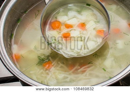 chicken soup with vegetables cooked in a pan. ladle soup