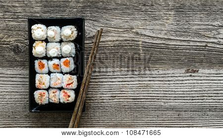 assorted sushi on black plate with chopsticks on wooden background