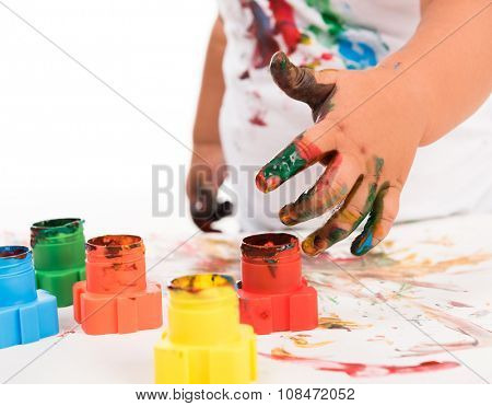 painted child's hand and colors isolated on white background