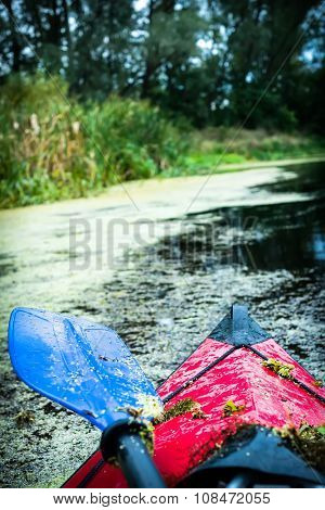 red kayak floating on a river